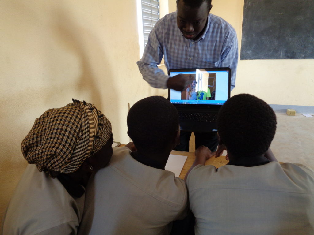 Teacher holding computer and pointing to images while students lean in